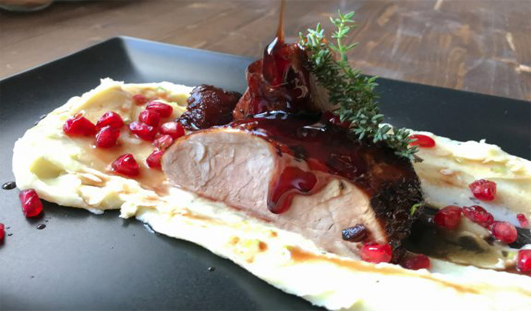 Pork tenderloin on mashed potatoes and pomegranate sauce